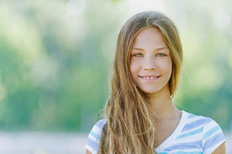 A beautiful smiling teenager standing in front of a park in blue blouse st