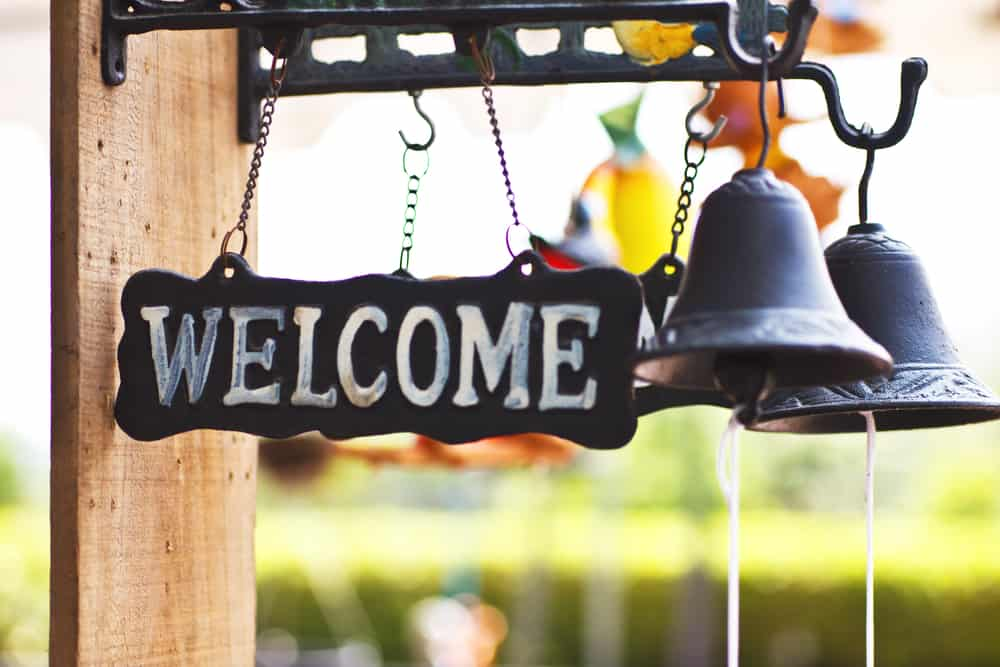 a welcome sign hanging outside a house