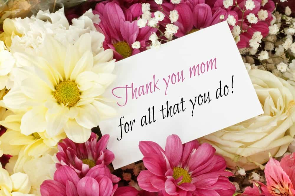 A note saying thank you mom surrounded by pink and yellow flowers