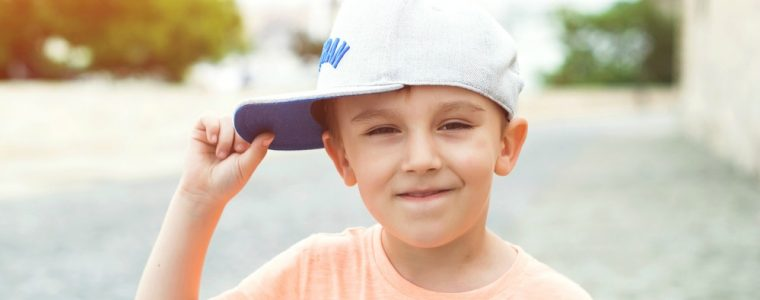a 5 year old standing outside holding his hat to the side