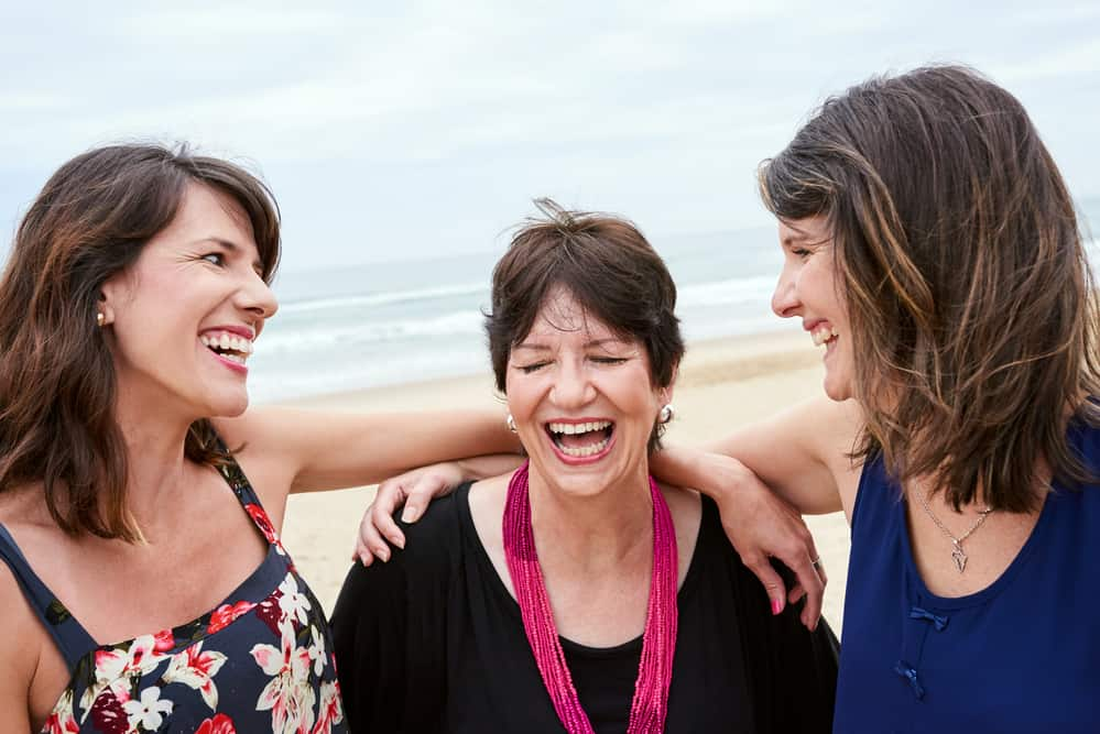 a mom and her 2 daughters laughing on the beach