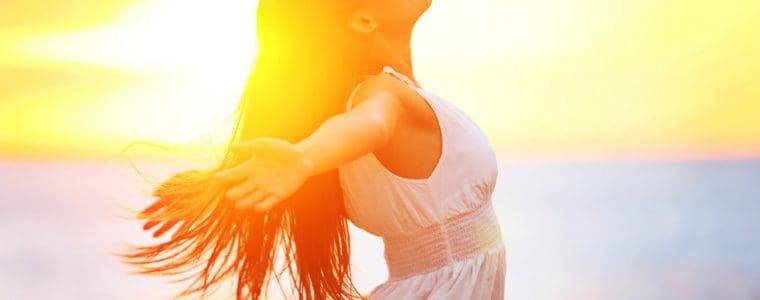 Beautiful woman in a white dress embracing the golden sunshine