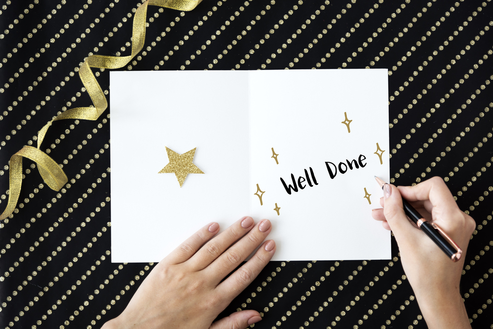 Card on a black backgrounds saying well done