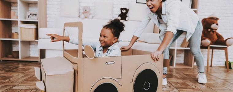 babysitter playing with kid in cardboard car
