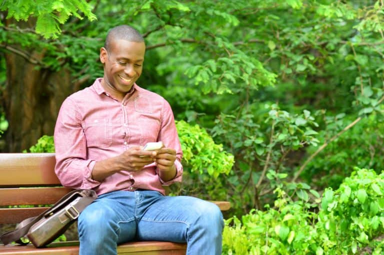 Happy male sending message on his phone