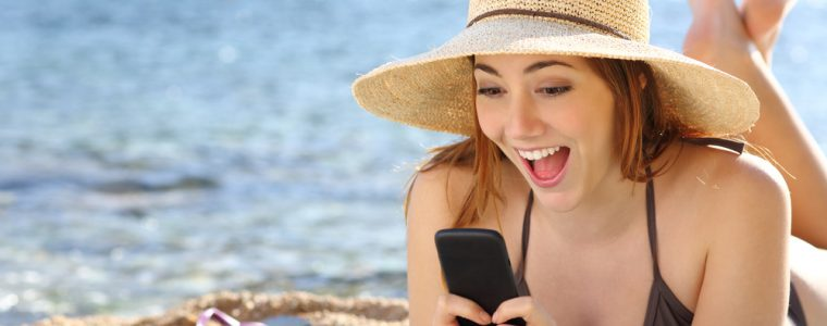 Young girl laughing at phone on beach
