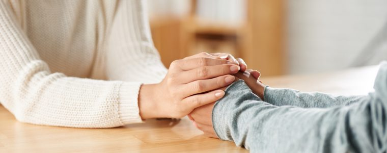 Two women holding hands grieving over loved one