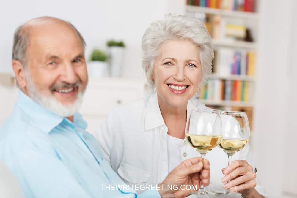 Happy senior couple CELEBRATING ANNIVERSARY WITH white wine