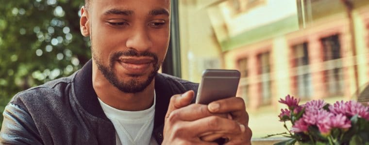 African American reading text message at a cafe