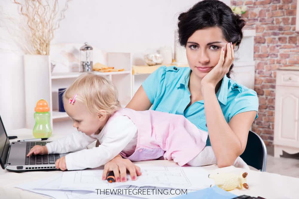 Young busy mom with laptop and her baby girl