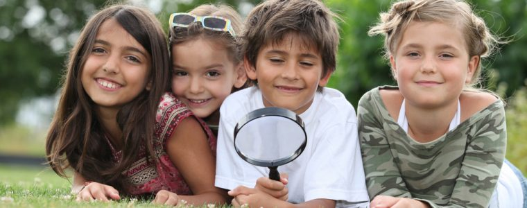 Kids enjoying an adventure in the park with magnifying glass